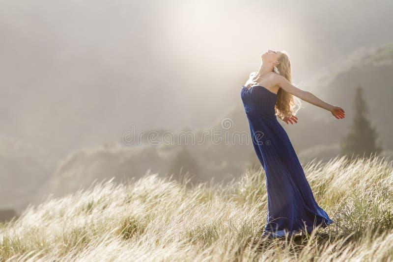 Внешний портрет молодой красивой женщины в голубой мантии представляя дальше стоковое фото rf