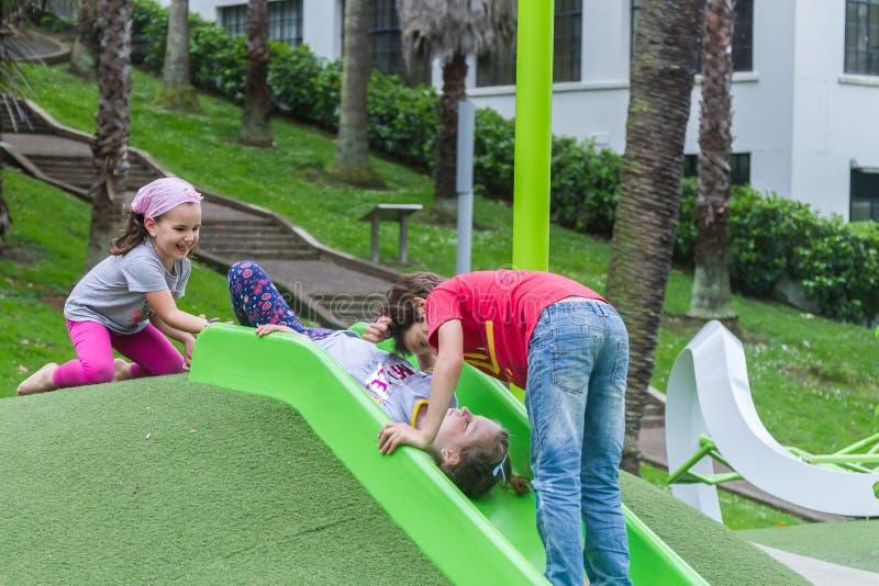 Внешний портрет молодых счастливых детей на спортивной площадке стоковое изображение
