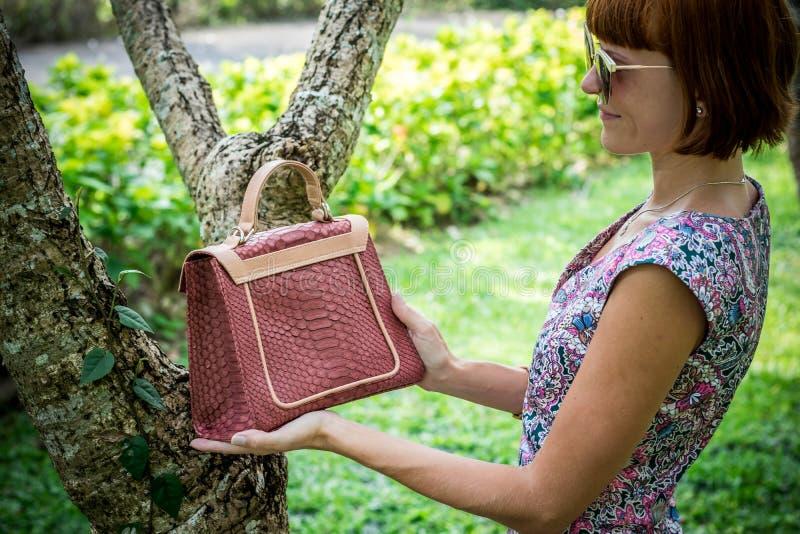 Внешний портрет моды дамы очарования чувственной молодой стильной в солнечных очках с роскошной handmade сумкой питона snakeskin стоковое фото
