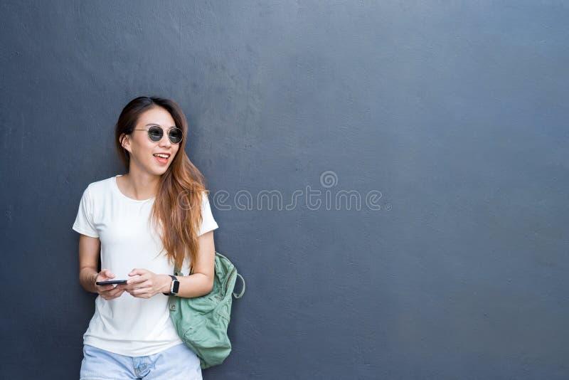 Внешний портрет образа жизни довольно сексуальной молодой азиатской девушки в перемещении и стиле стекел на серой предпосылке сте стоковые изображения