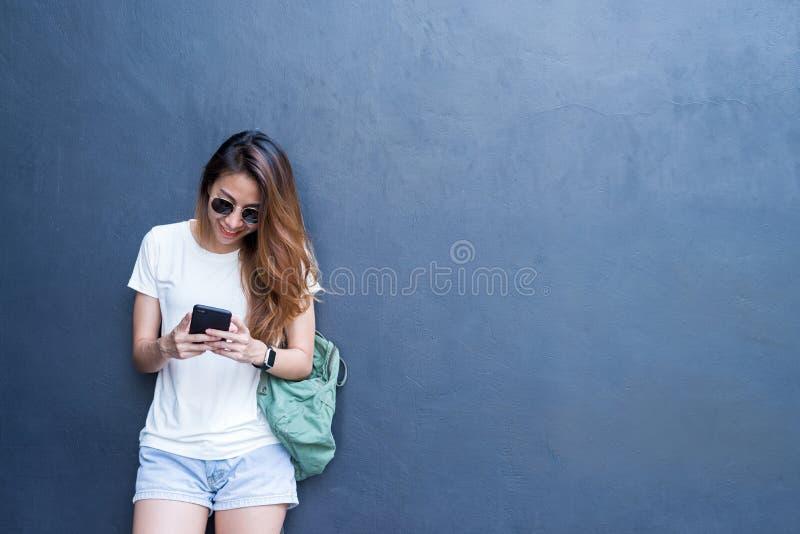 Внешний портрет образа жизни довольно сексуальной молодой азиатской девушки в перемещении и стиле стекел на серой предпосылке сте стоковые фото