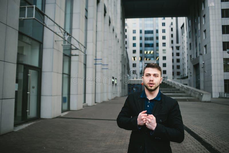Внешний портрет серьезного молодого бизнесмена с бородой против фона красивой современной архитектуры стоковые фото