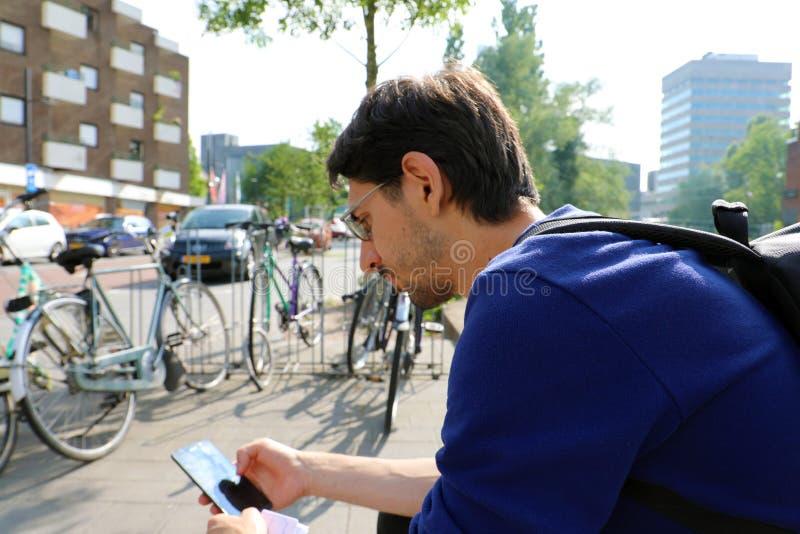 Внешний портрет современного молодого человека сидя с мобильным телефоном в Эйндховене, Нидерландах стоковые фотографии rf
