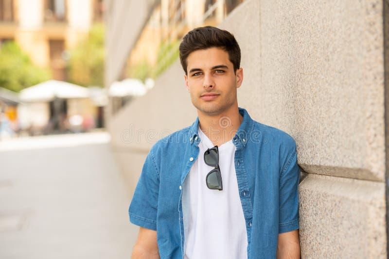 Внешний портрет современного привлекательного молодого человека в городе предпосылка урбанская стоковое фото
