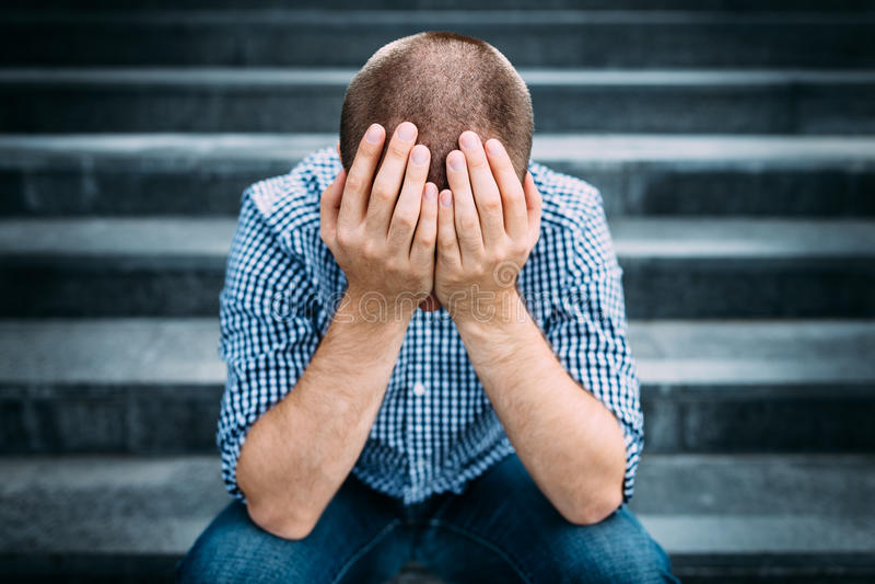 Внешний портрет унылого молодого человека покрывая его сторону с руками стоковые фотографии rf