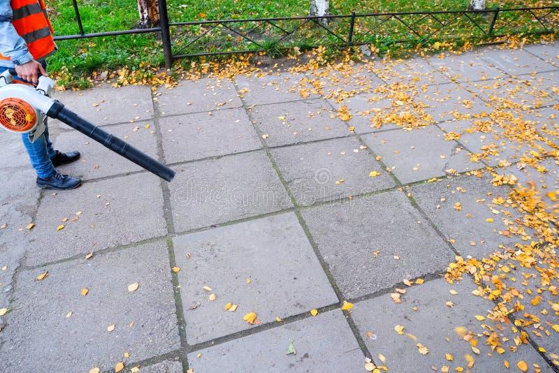 Внешний работник физического труда очищает упаденные листья на дороге воздуходувкой в осени стоковые изображения