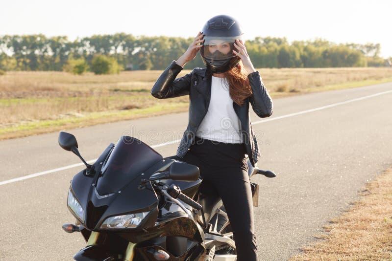 Внешняя съемка быстрого женского мотоциклиста носит защитный шлем, представляет на мотоцикле, стойках на мотоцикле, покрывает меж стоковое изображение rf