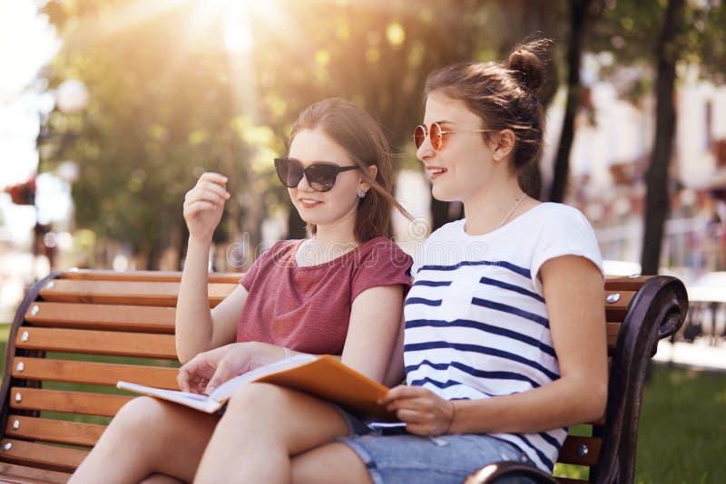 Внешняя съемка жизнерадостных женских друзей, имеет нежные улыбки, подготавливает для окончательного экзамена совместно, сидит на стоковое фото