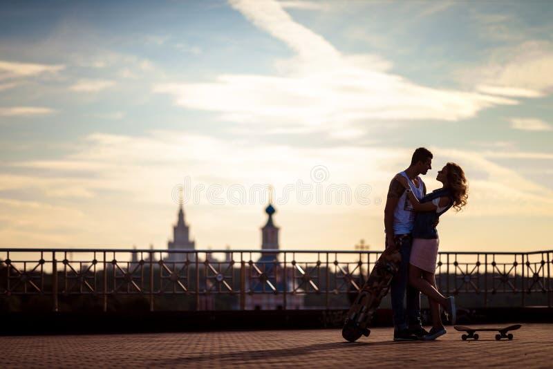 Внешняя съемка ласковых молодых пар представляет против красивого вида на город и небо, имеет остатки после skateboading стоковое изображение rf