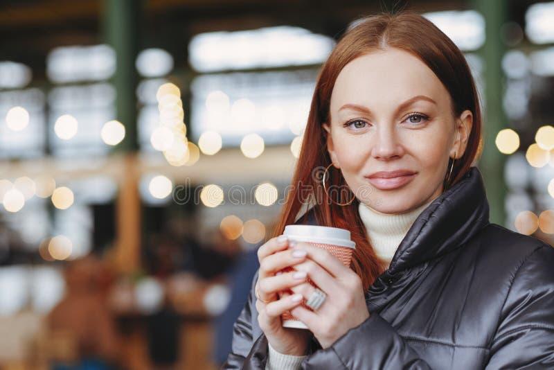 Внешняя съемка удовлетворенной привлекательной женской модели со здоровой кожей, каштановыми волосами, кофе владениями на вынос,  стоковая фотография