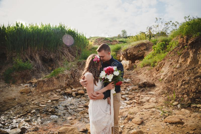 Внешняя церемония свадьбы на пляже, стильный счастливый усмехаясь groom и невеста стоящ и обнимающ около малого реки стоковая фотография