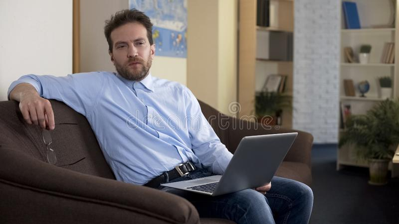 Внештатный автор сидя с ноутбуком дома, думающ о вопросах работы стоковые фото