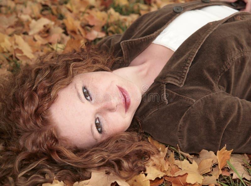 вниз лежа женщина redhead стоковое фото rf