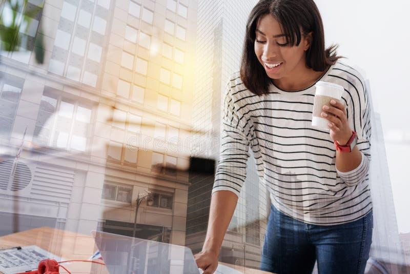 Внимательная женская персона работая с компьютером стоковое фото
