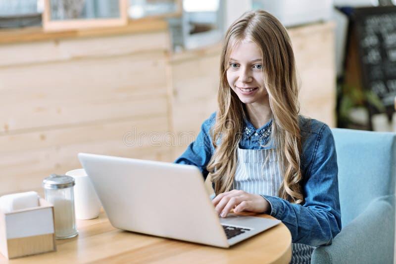 Внимательная женская персона работая с компьютером стоковое изображение