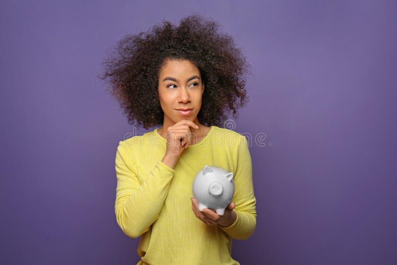 Внимательная молодая Афро-американская женщина с копилкой на предпосылке цвета Концепция сбережений стоковое изображение