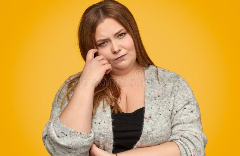 Внимательная пухлая женщина царапая сторону стоковые фото
