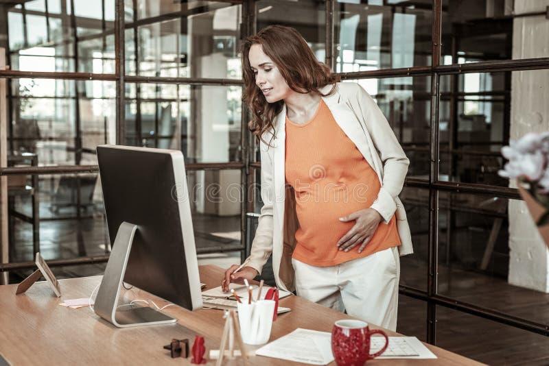 Внимательное темн-с волосами положение женщины перед компьютером стоковые фотографии rf