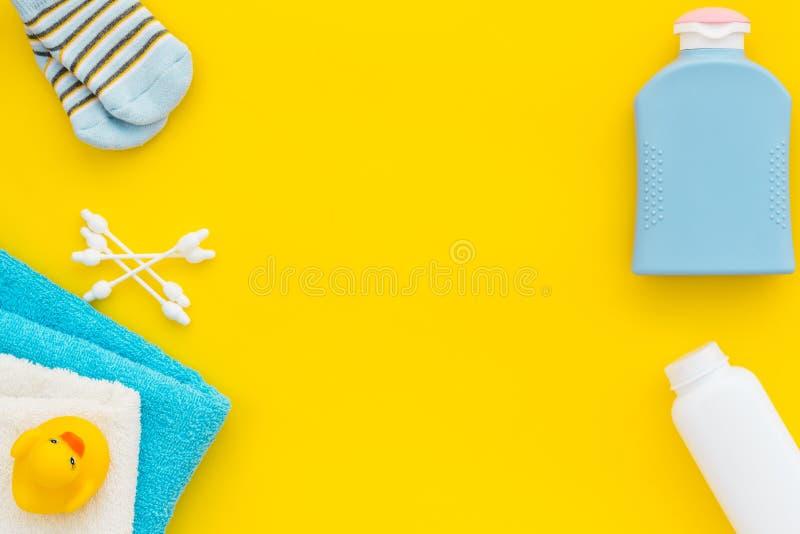 Внимательность младенца Косметики и аксессуары ванны для ребенка Шампунь, гель, сливк, гребень, желтая резиновая утка на желтой п стоковые изображения rf