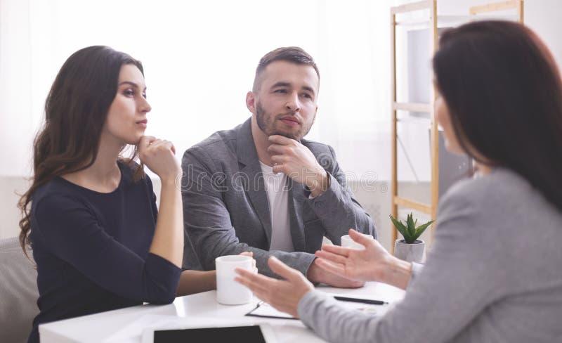Внимательные молодые пары слушая уверенный финансовый советника стоковое фото rf