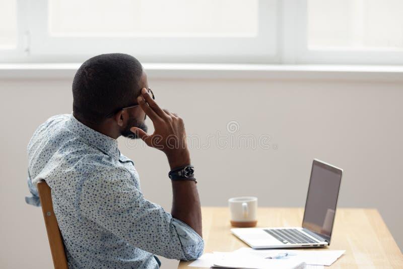 Внимательный Афро-американский бизнесмен смотря вне усаживание окна на офисе стоковые изображения rf