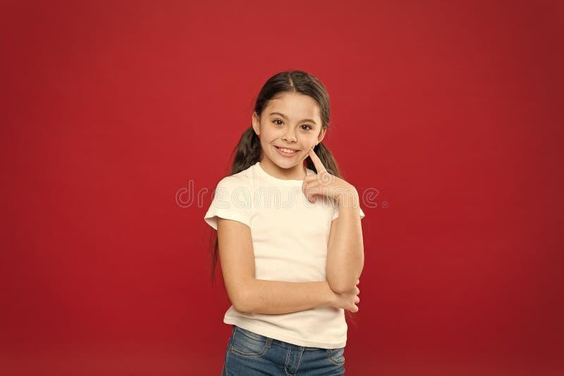 Внимательный взгляд модели skincare Небольшая девушка держа палец на коже щеки Прелестная маленькая девочка без макияжа : стоковые фотографии rf