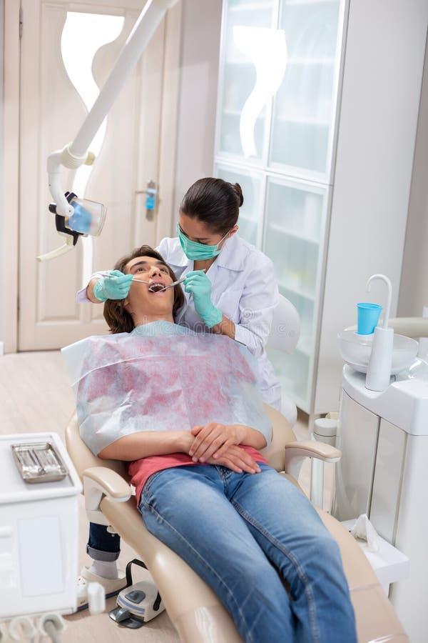 Внимательный женский рассматривать доктора молодые пациенты изрекает стоковые изображения