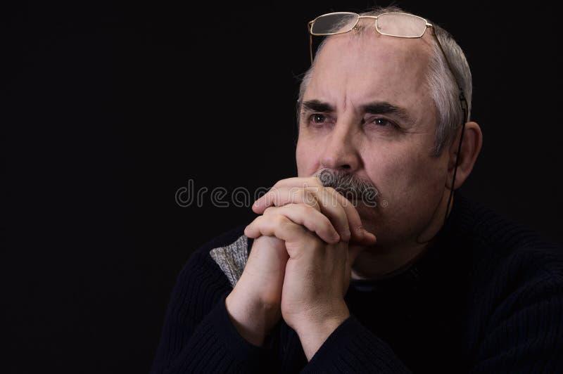 Внимательный кавказский человек против черной предпосылки стоковое изображение