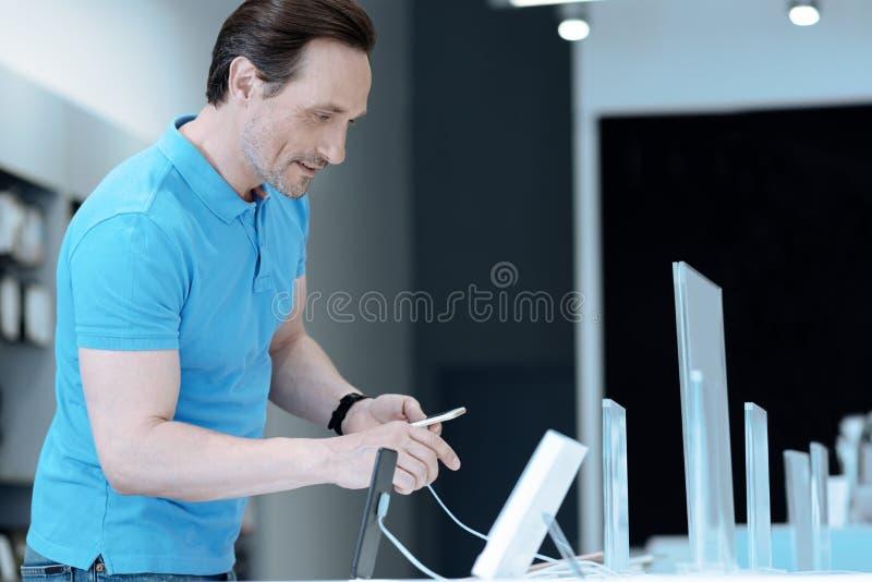 Внимательный мужск человек ища новый телефон стоковая фотография