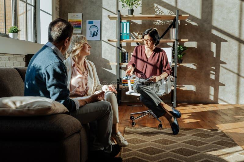 Внимательный темн-с волосами терапевт сидя с тетрадью на стуле офиса стоковая фотография