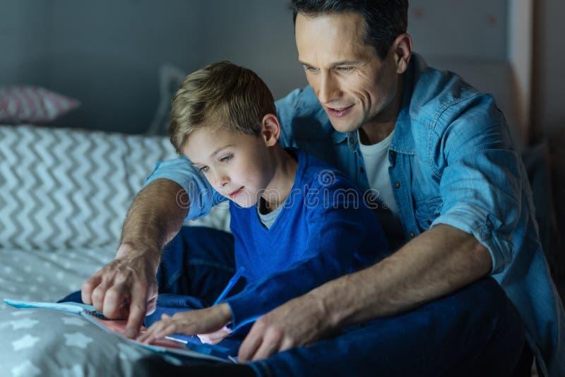 Внимательный человек делая задачу с его сыном стоковые фото