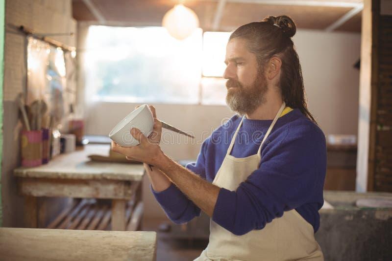 Внимательная мужская картина гончара на шаре стоковое изображение