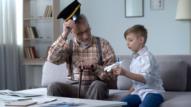 Внук играя с самолетом игрушки, дед в крышке салютуя к меньшему пилоту стоковое изображение rf