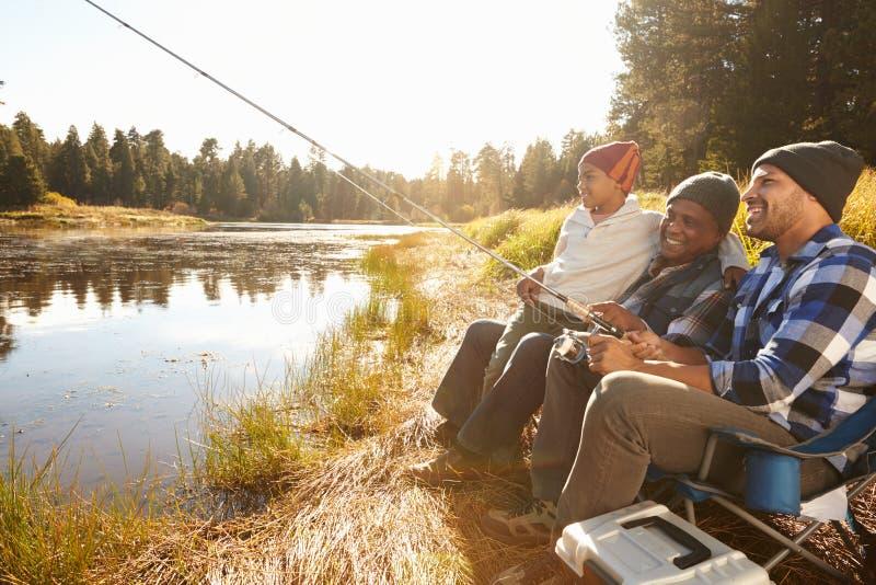 Внук с рыбной ловлей отца и деда озером стоковая фотография rf