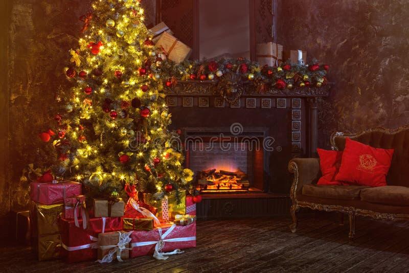 Внутреннее рождество волшебное накаляя дерево, камин, подарки в темноте вечером стоковое фото rf