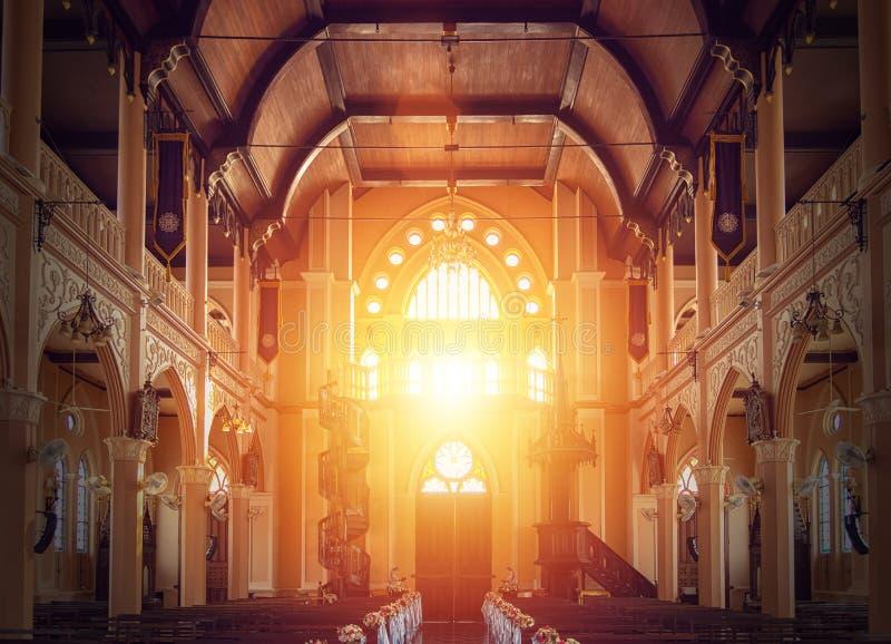 Внутренний взгляд пустой церков с деревянной скамьей украшенной с букетом цветка, солнечный свет через витраж церков стоковые изображения