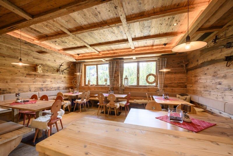 Внутренний взгляд удобной традиционной сельской деревянной гостиной тимберса со стульями стоковые фото