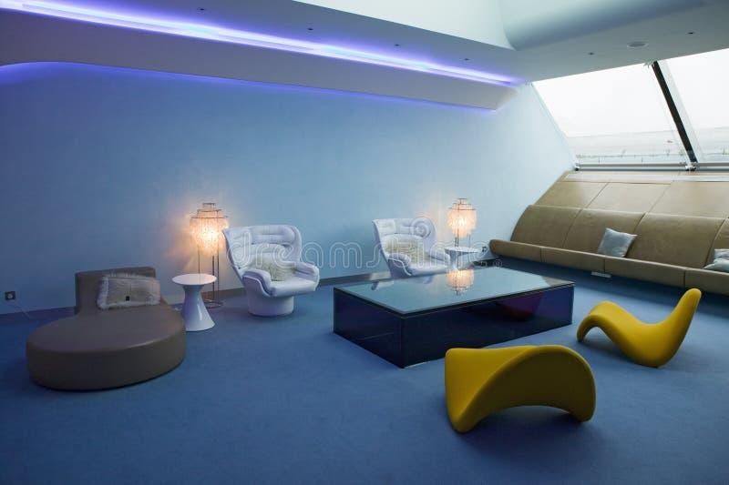 Внутренний взгляд современной мебели посадочных мест в салоне первого класса авиакомпаний девственницы на авиапорте Хитроу в Лонд стоковое изображение rf