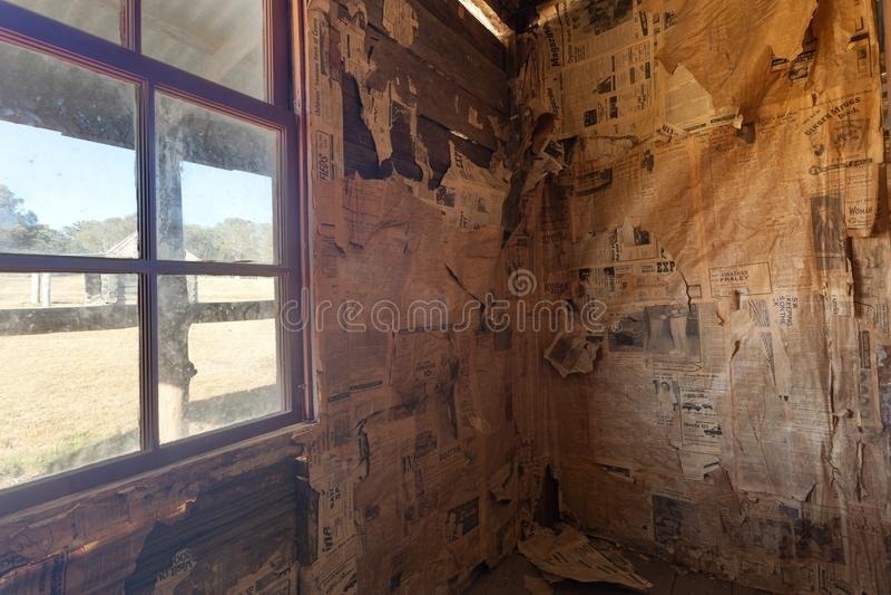 Внутри детали старой деревенской хижины выровнянной с газетой стоковые фото