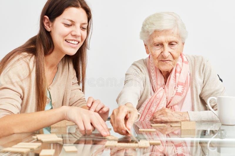 Внучка играет домино с бабушкой стоковое изображение rf