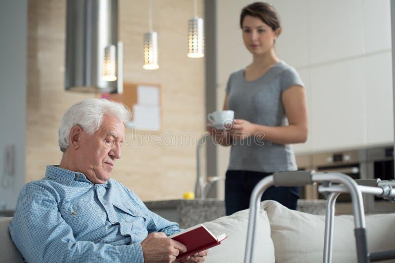 Внучка помогая ее неработающему grandpa стоковые фотографии rf