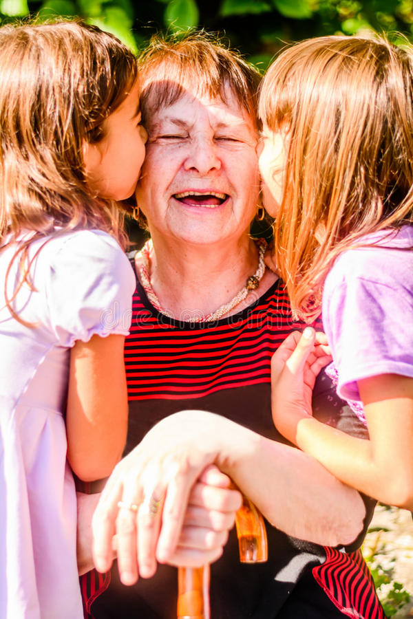 Внучки целуя их старую бабушку стоковая фотография