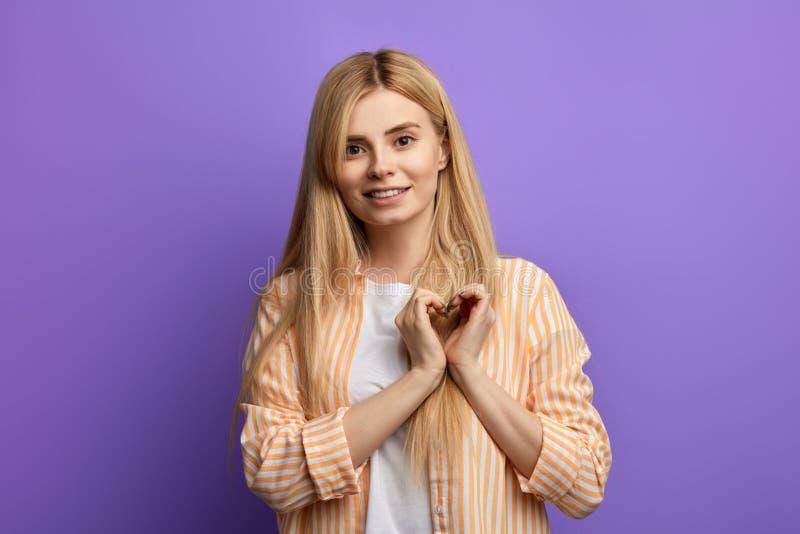 Внушительная девушка в striped рубашке и белой футболке показывая сердце с 2 руками стоковое изображение
