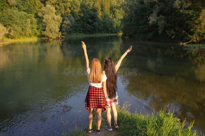 Внушительная девушка с поднятыми оружиями счастлива по мере того как они достигали озеро стоковое изображение
