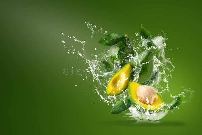 Вода брызгая на свежем отрезанном зеленом авокадое над зеленой предпосылкой стоковая фотография rf