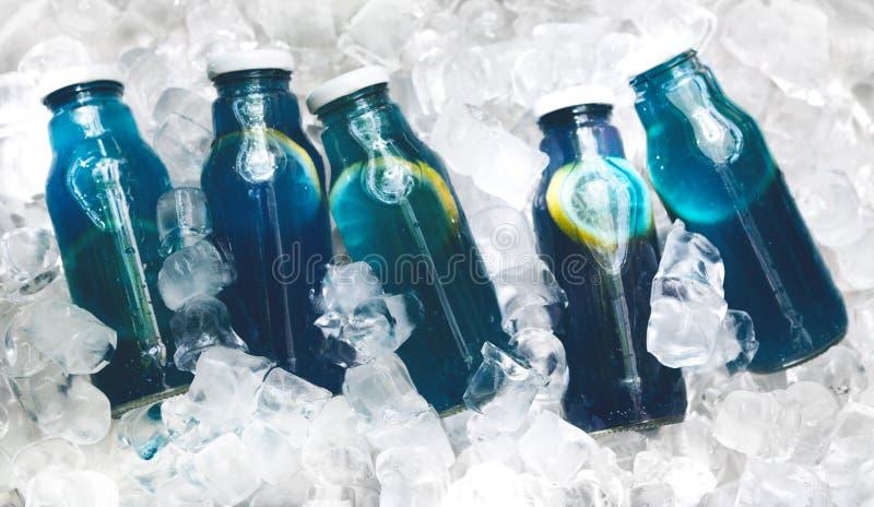 Вода вытрезвителя плода голубая в стеклянных бутылках для продажи на льде стоковая фотография