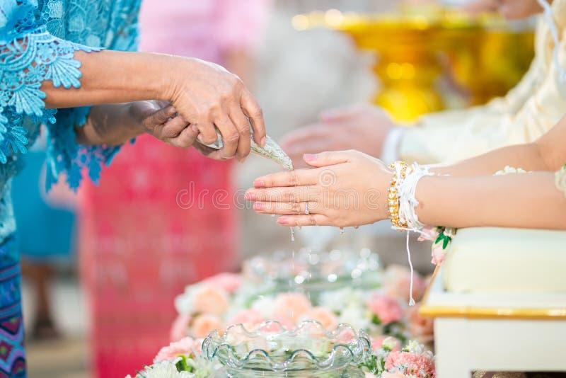 Вода гостя лить с руками жениха и невеста в церемонии выпуска обновленного изделия воды Тайская традиционная свадьба стоковая фотография rf