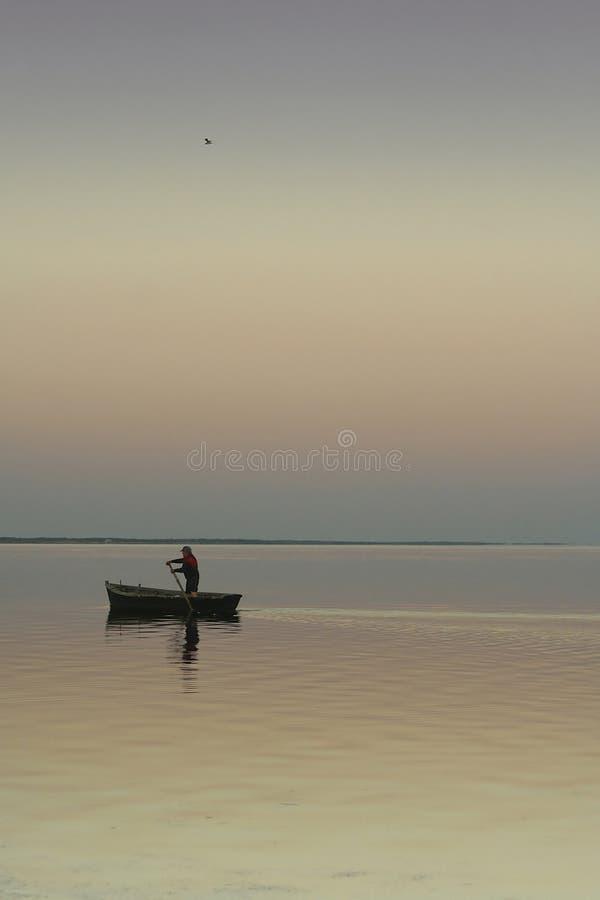 вода захода солнца шлюпки сиротливая молчком стоковое изображение