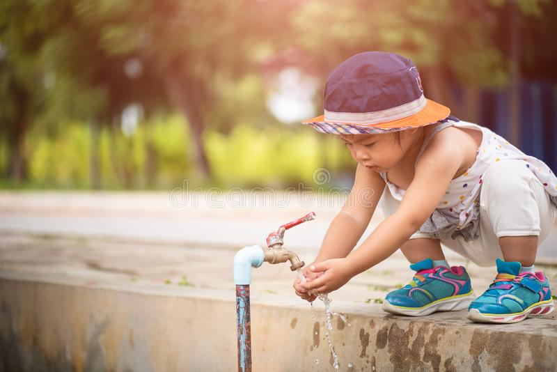Вода лить в руках ` s маленькой девочки стоковая фотография rf