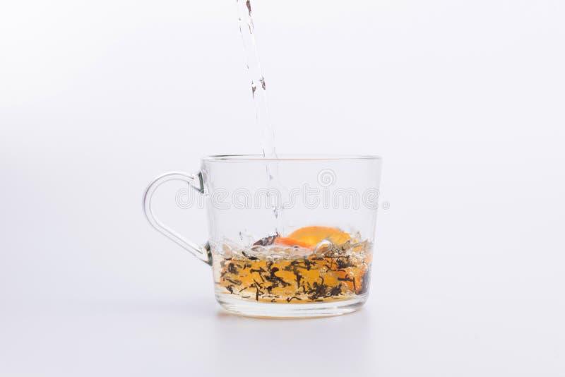 Вода лить в стеклянную чашку с черным чаем и лимоном изолированными на белизне стоковые изображения